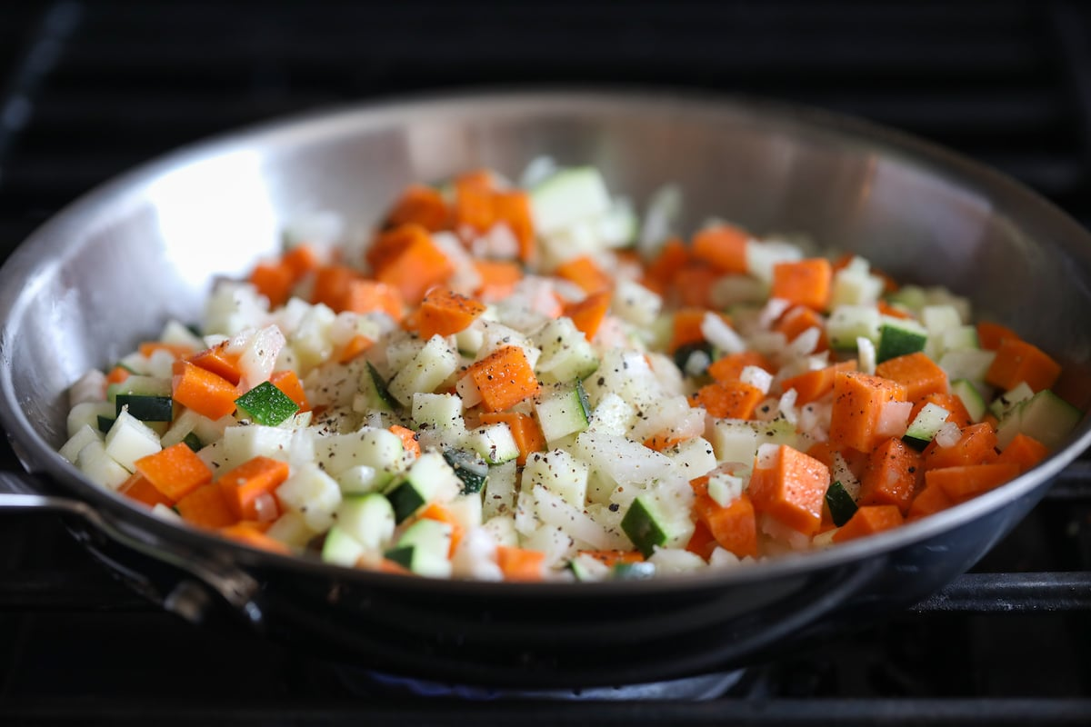 onion, carrot and zucchini in skillet