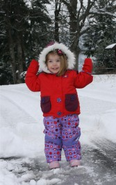 A little girl that is standing in the snow