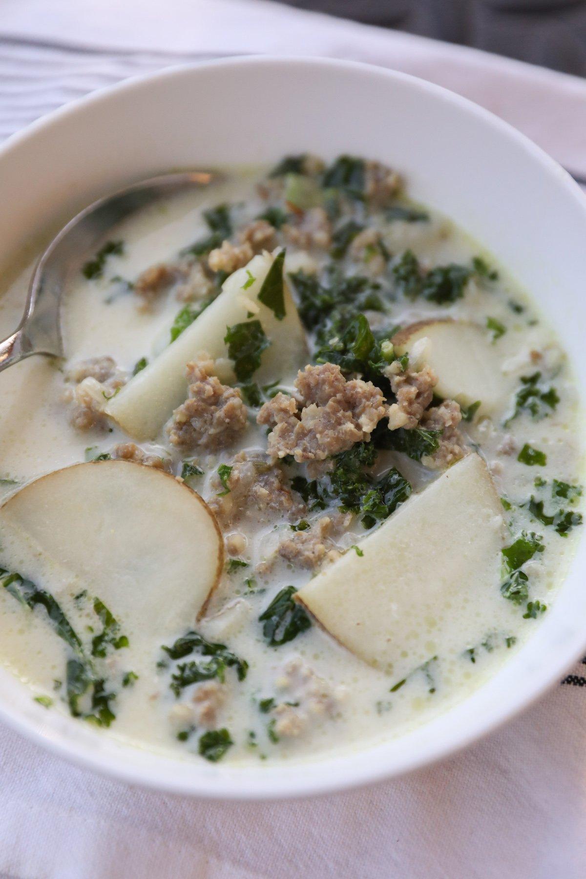 sausage kale soup in white bowl