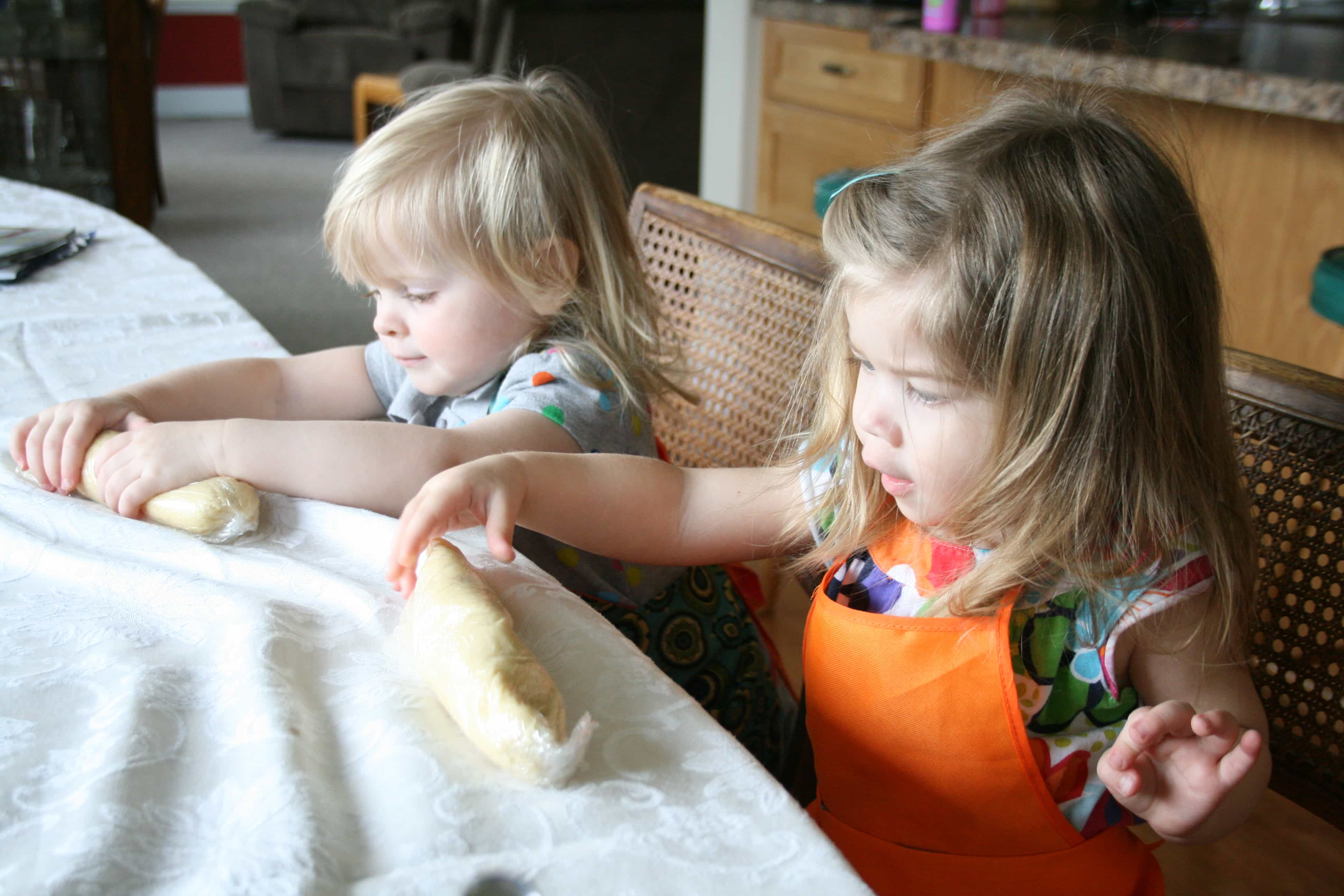 Brooke and cousin rolling up sugar cookie dough
