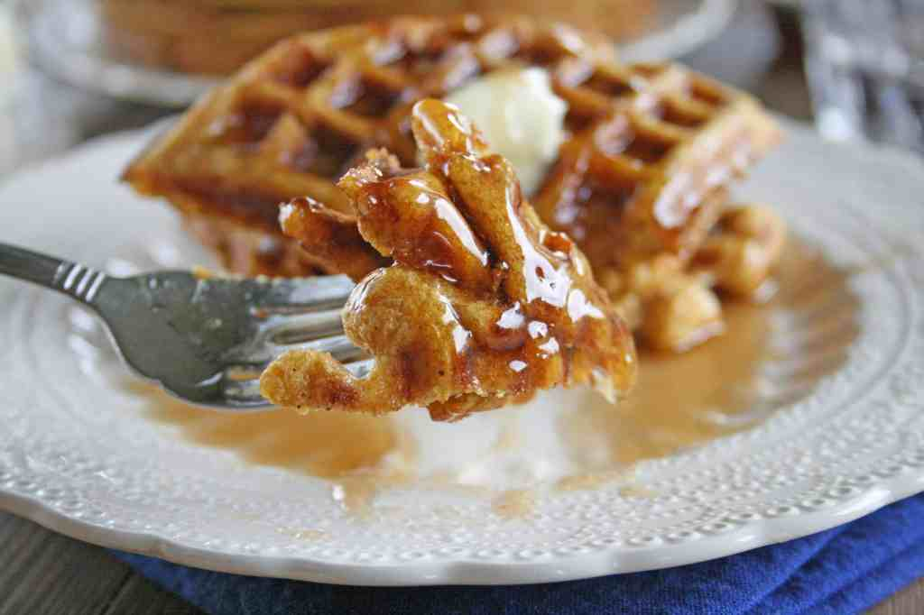 a forkful of healthy pumpkin waffle with the stack behind it on a plate