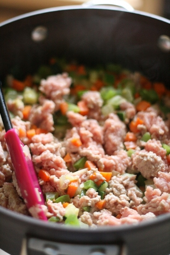 adding ground turkey to cooked vegetables