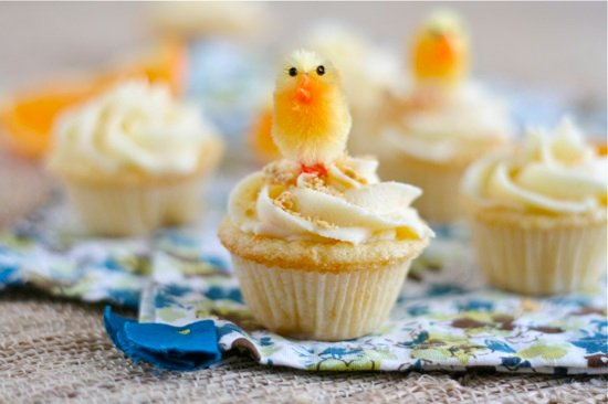 Orange cupcakes with orange frosting on top and a little decorative chick