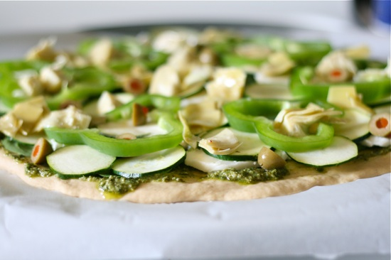 Sliced bell peppers and zucchini on top of unbaked pizza