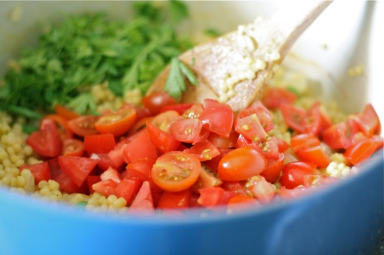 Adding tomatoes and cilantro to couscous