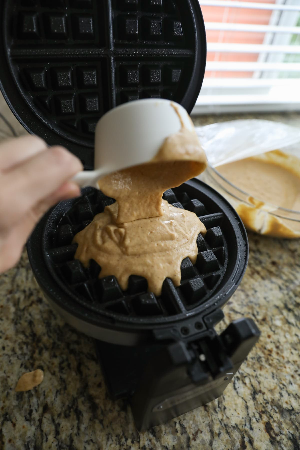 pouring batter into hot waffle iron