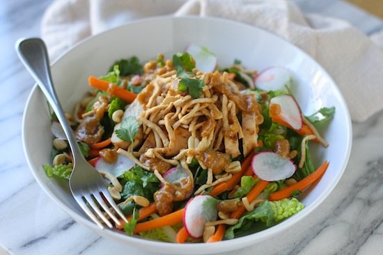 thai chicken salad in a white bowl with a metal fork