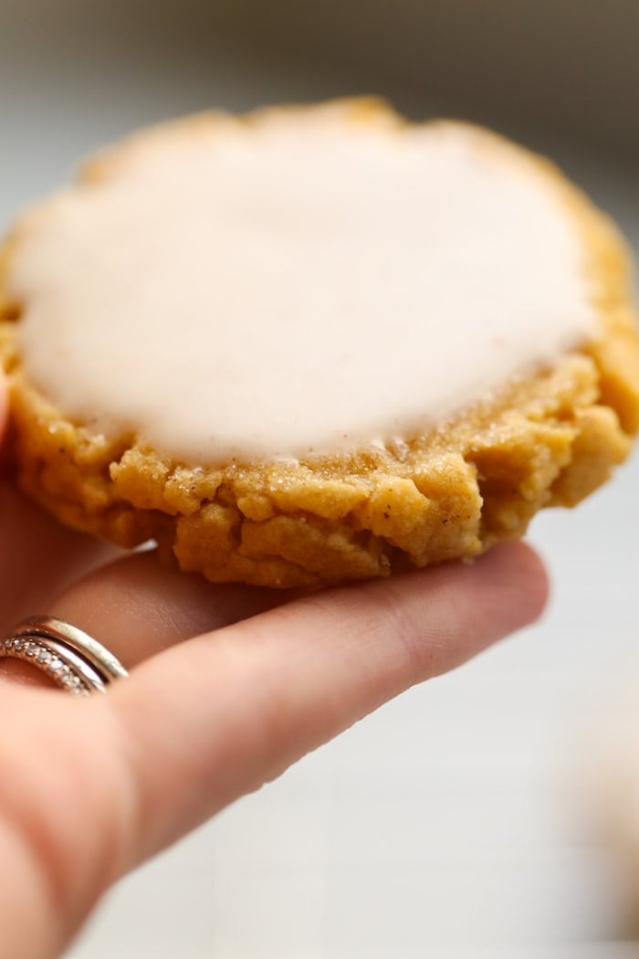 hand holding a pumpkin sugar cookie with icing