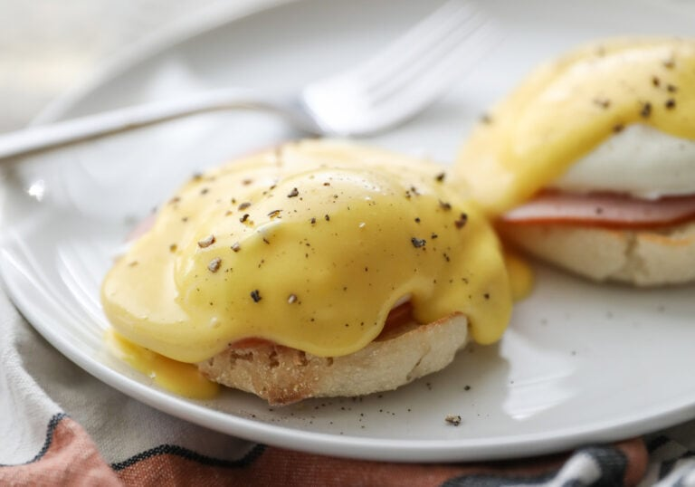 Eggs Benedict on white plate with fork
