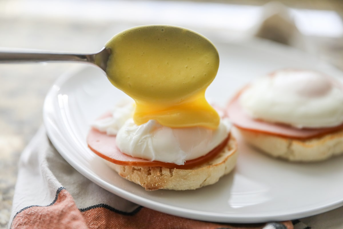pouring hollandaise sauce over poached egg