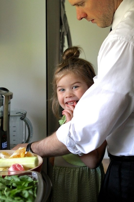 little girl smiling at the camera while standing at the counter