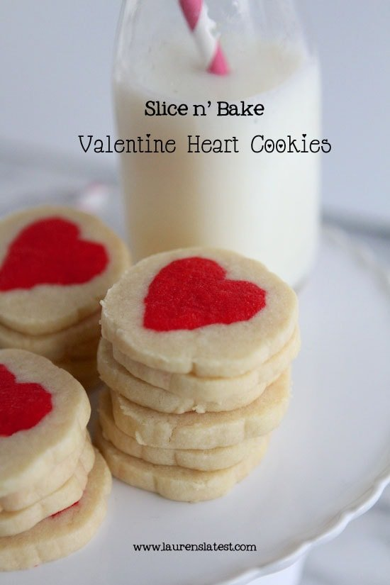 valentine's slice and bake cookies stacked on top of each other on a white cake plate with milk