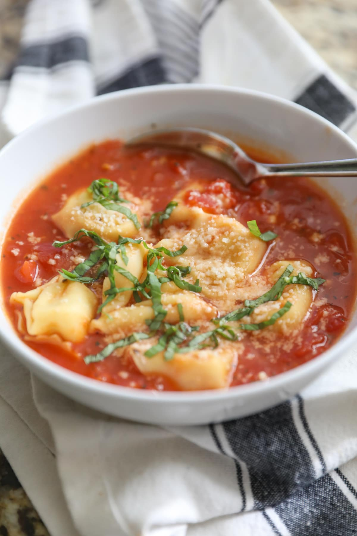 tomato basil tortellini soup in white bowl
