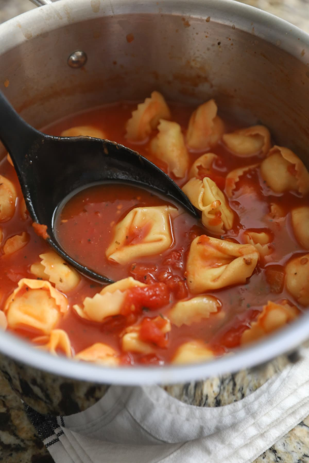 ladling tortellini soup out of pot