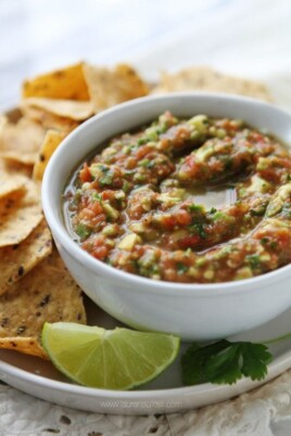 teedo's famous salsa in a bowl with chips and lime on the side