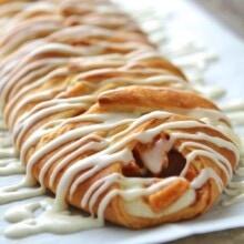 cinnamon apple cream cheese danish with icing on a baking pan