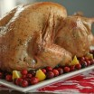 roast turkey on a platter with cranberries and lemon wedges