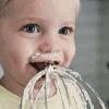 little boy licking a whisk