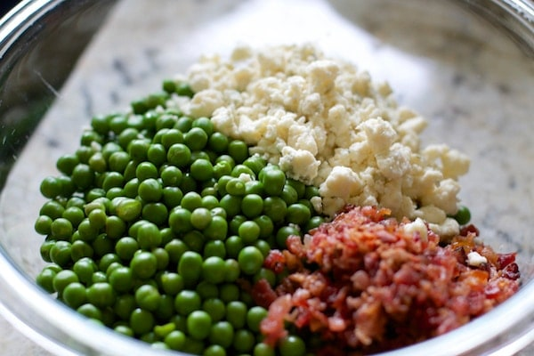 Peas bacon and blue cheese in a glass bowl