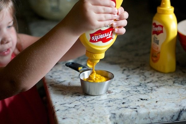 Squeezing mustard into measuring cup