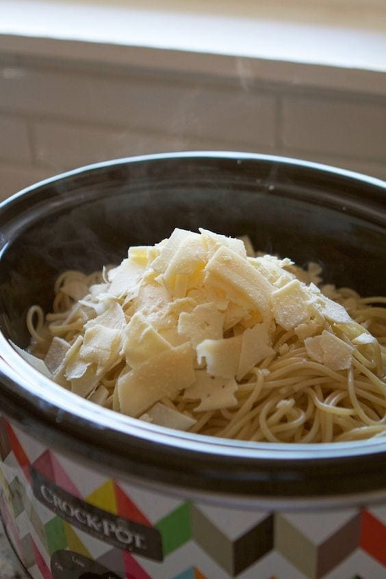 Spaghetti and cheese in crockpot on top of sauce and chicken