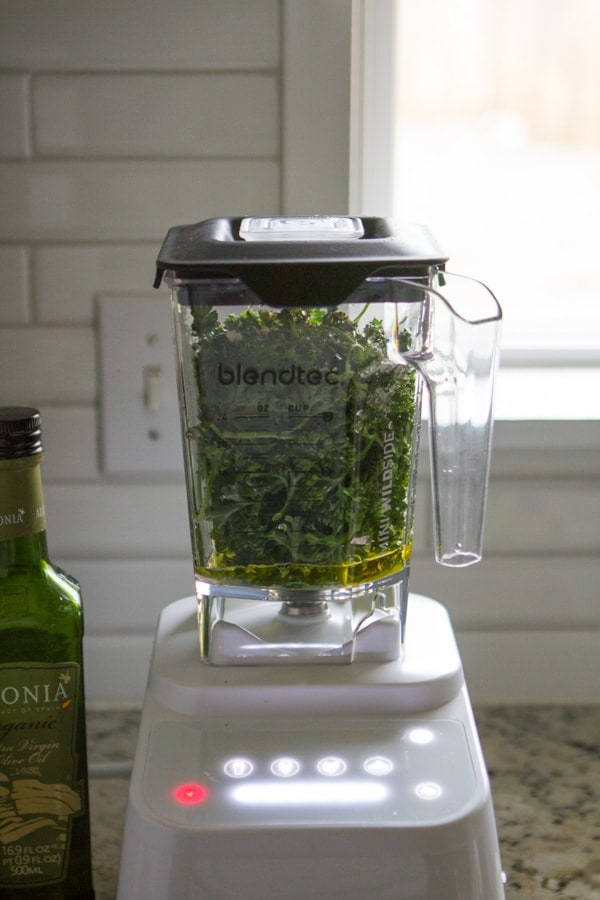 Blender with greens in it and other ingredients