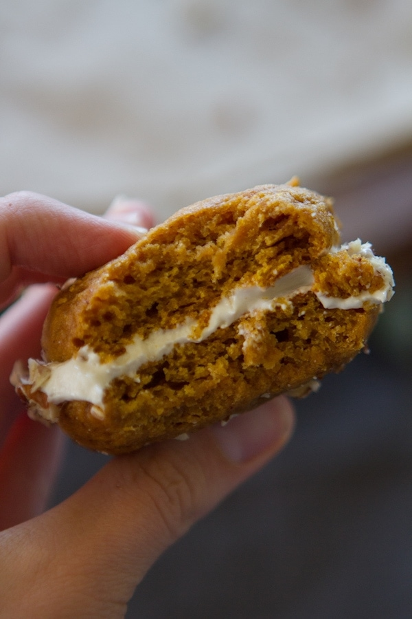 hand holding pumpkin whoopie pie with bite missing