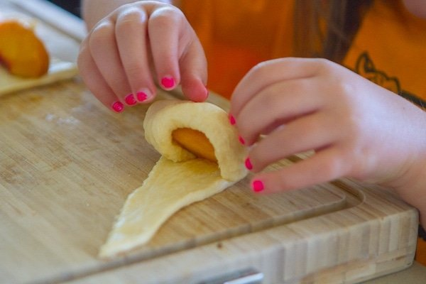 Rolling up peach on crescent roll triangle