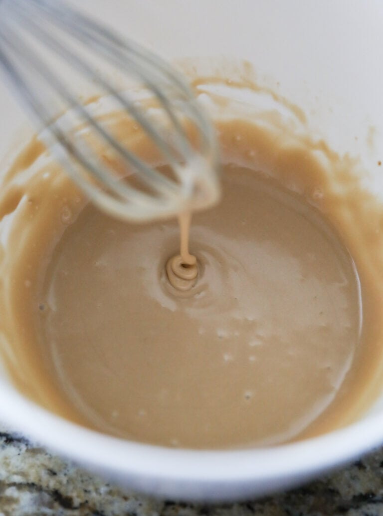 whisking maple glaze in white bowl