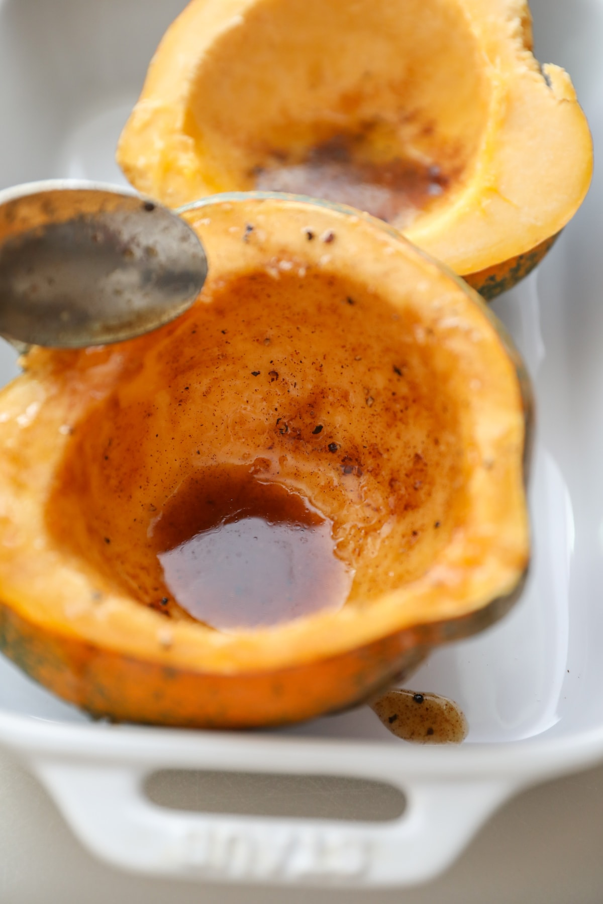 spooning melted butter and maple syrup on acorn squash