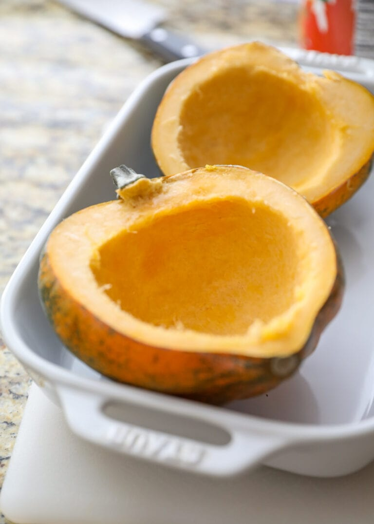 halved acorn squash cleaned out in white baking pan
