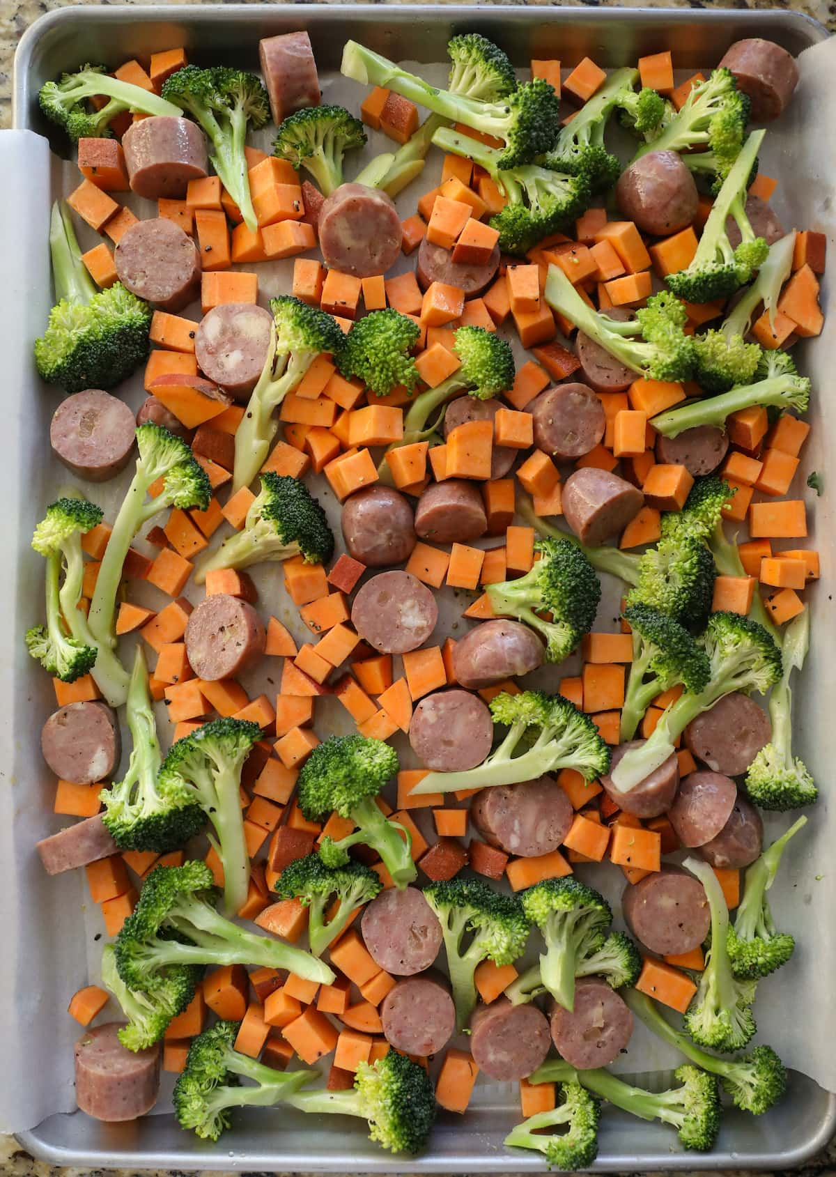 sausages and vegetables on baking sheet before roasting