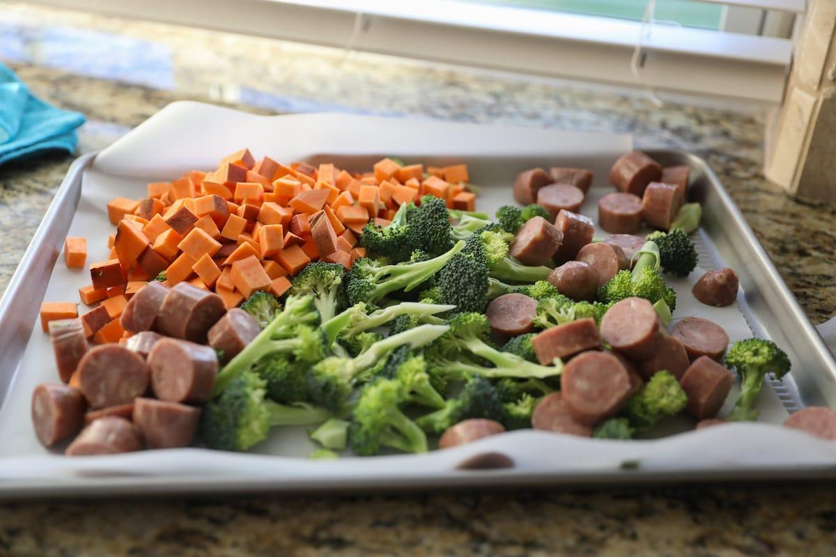 Broccoli, sweet potato and chicken sausage on baking sheet