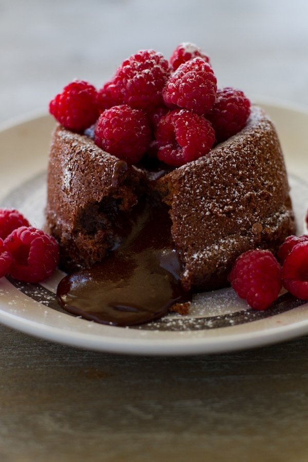 Lava Cake oozing out chocolate with raspberries and powdered sugar on top