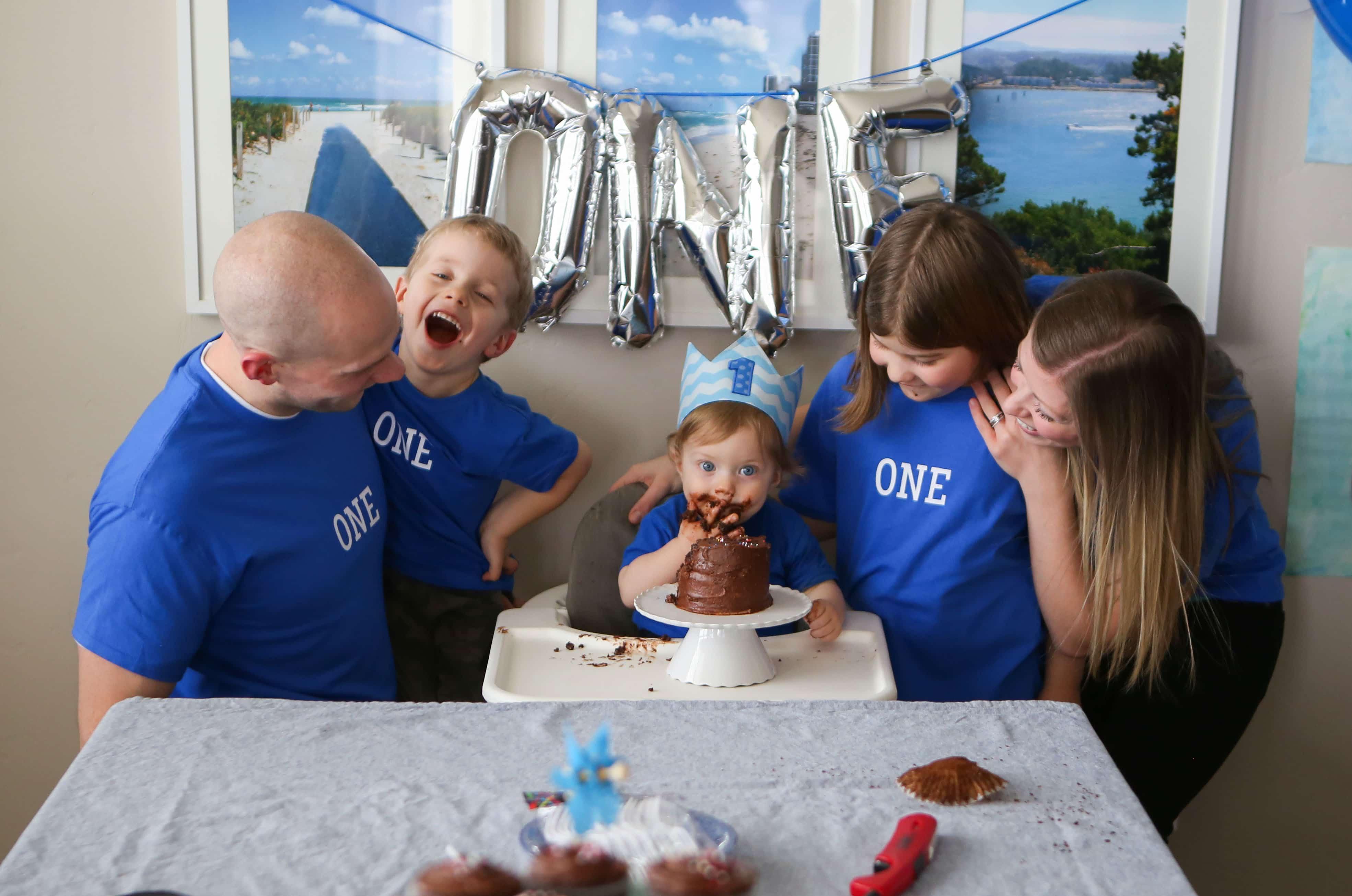 Brennan family surrounding Eddie eating cake