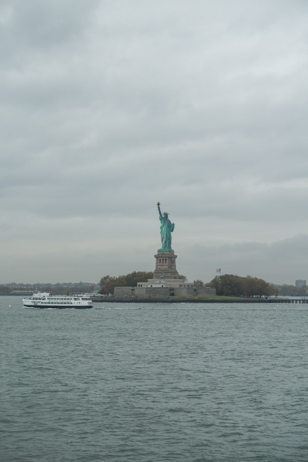 A large ship in a body of water with the statue of liberty
