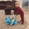 Blake pushing Eddie on a toy