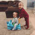 Blake pushing Eddie on a toy