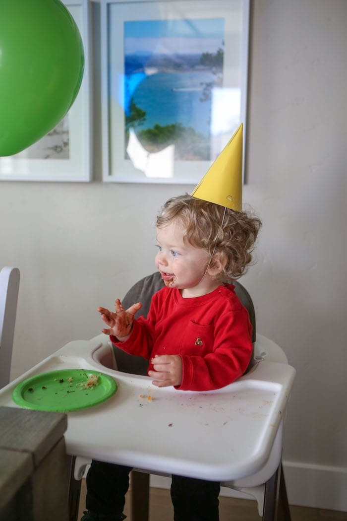 Eddie in a high chair eating cake