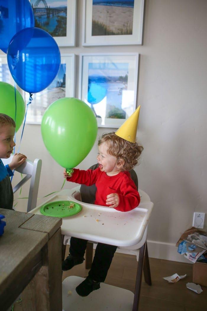 Eddie in a high chair holding a balloon