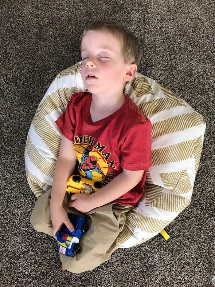 Blake asleep on the ground holding toys