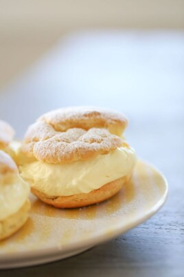 lemon cream puffs on a white plate dusted with powdered sugar