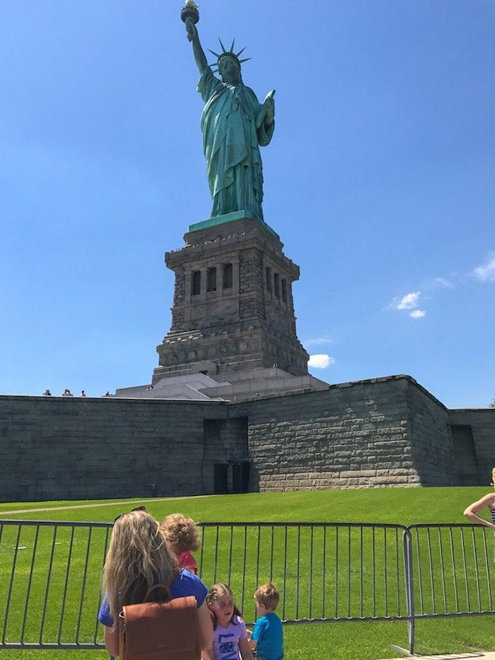 Lauren holding Eddie in front of the Statue of Liberty