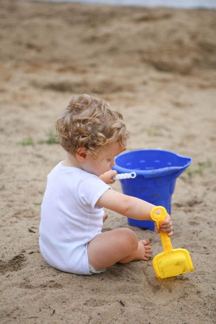 A little boy sitting on top of a sandy beach