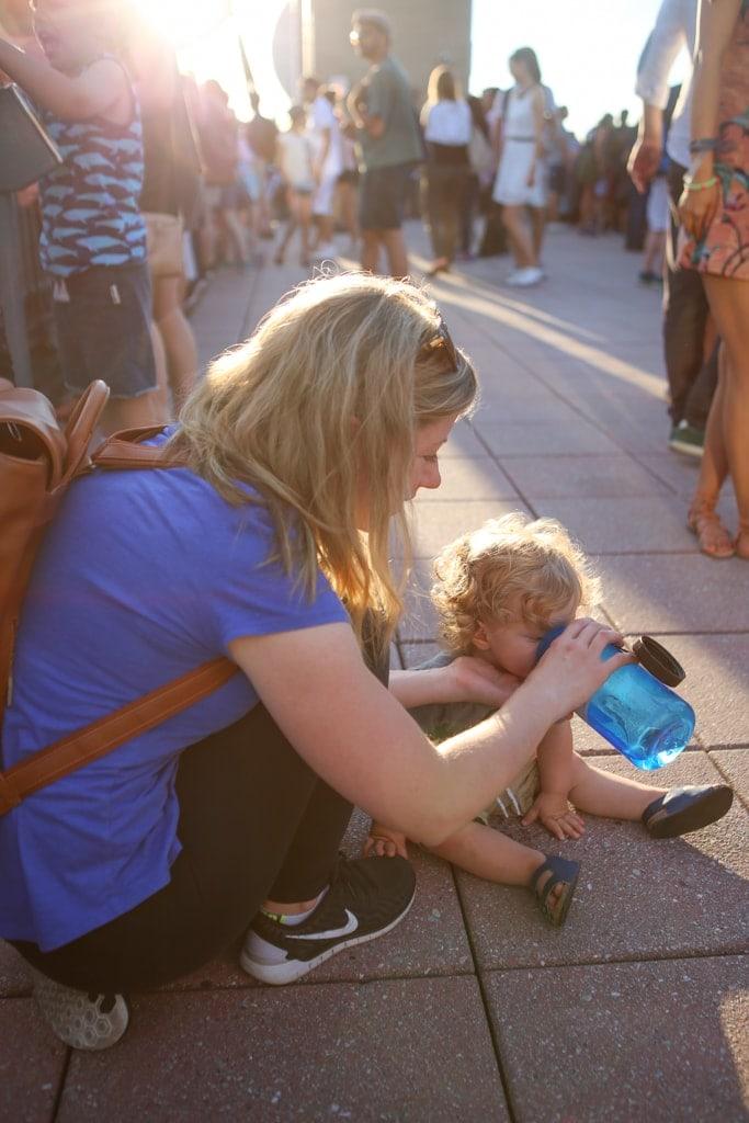 Lauren giving Eddie a drink of water on the ground