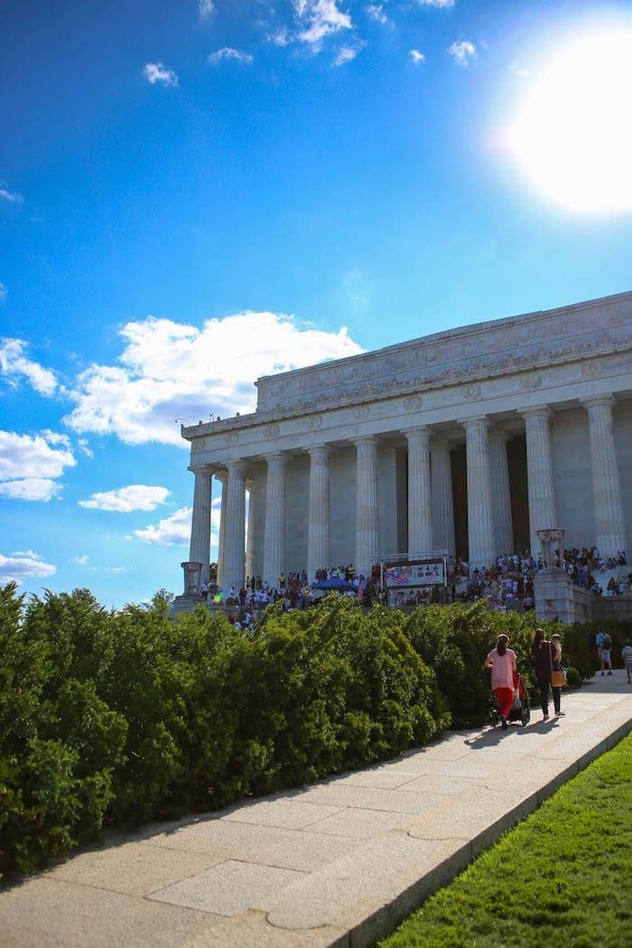 A person standing in front of a building, with Lincoln Memorial