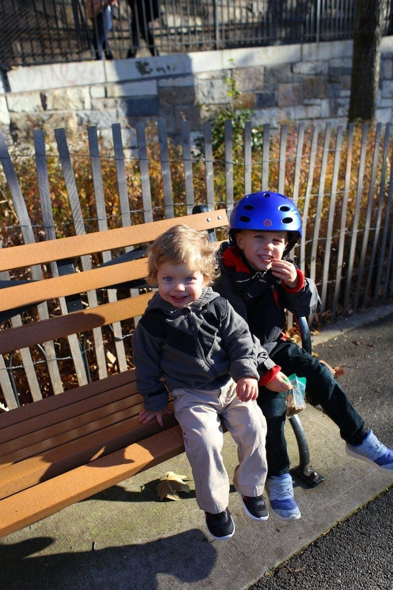 A little boy wearing a helmet and sitting on a bench