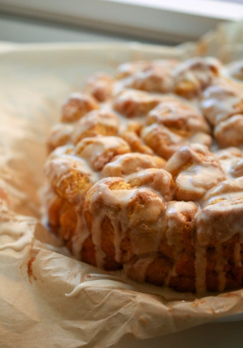 Pumpkin Monkey Bread with a glaze on parchment paper