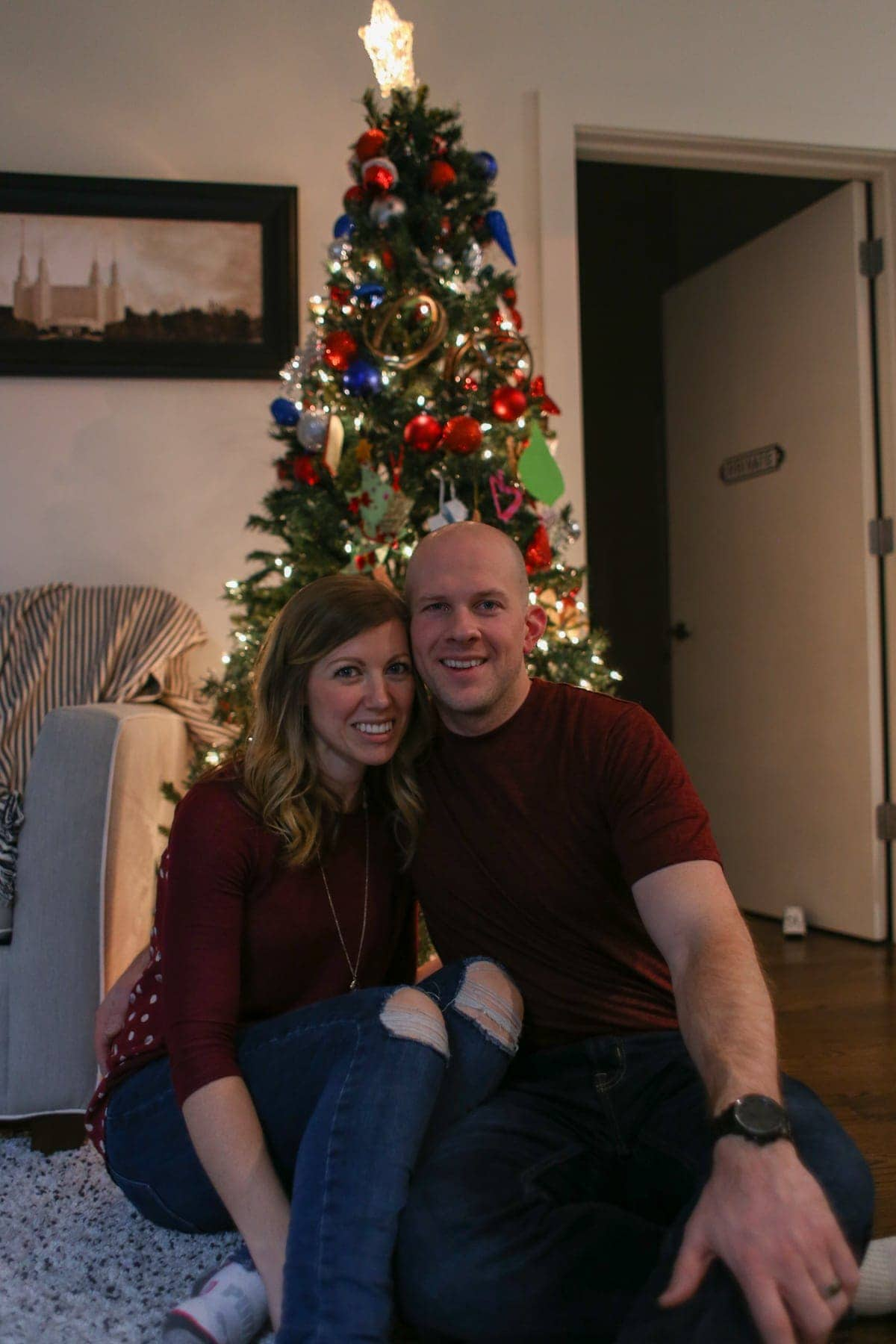 Lauren and Gordon in front of a Christmas tree in their home