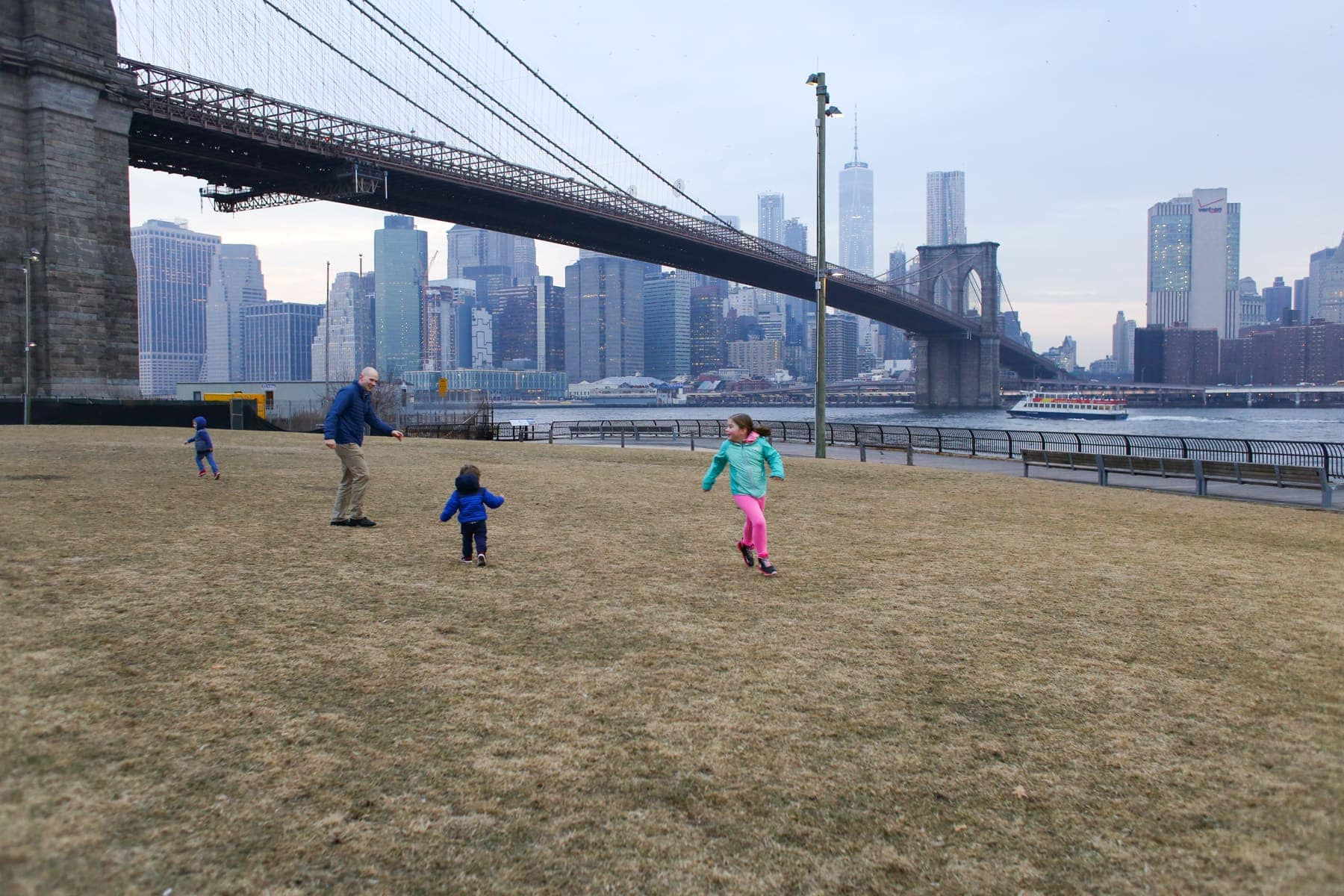 Brennan family playing in the grass with a bridge and city behind them